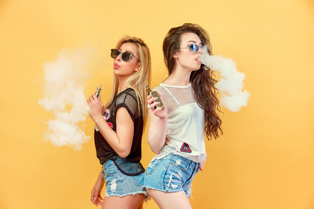 Side view of trendy young female in glasses and shorts standing and smoking on studio background Standard-Bild - 102133875