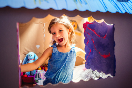 Content pretty little girl sitting inside of colored carton playhouse looking at camera smiling through small window.