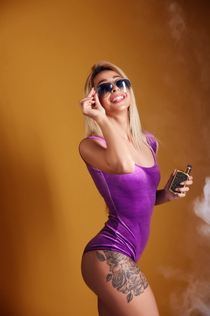 Hot young woman in sunglasses puffing vapor on yellow background in studio.