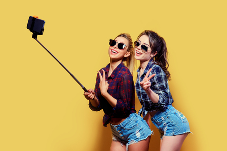 Fashion portrait of two friends. modern lifestyle. two stylish hipster girls best friends ready for party. Young girl friends standing together and having fun. Taking selfie on yellow background.