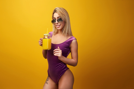 Side view of confident blond in sunglasses and pink bodysuit with tattoo on hip drinking refreshing cocktail on orange . Imagens
