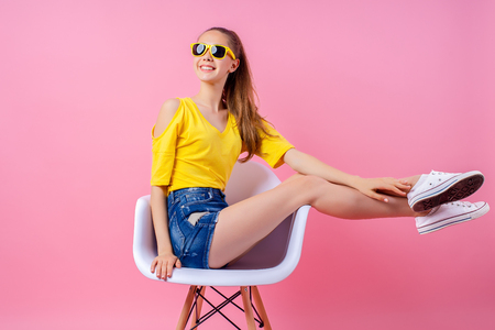 Smiling teenage female in sunglasses sitting in white chair in studio with legs raised on pink background