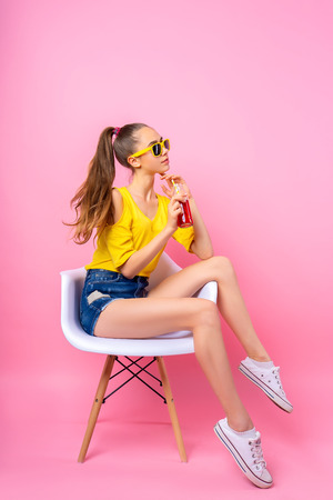 Adorable girl in sunglasses sitting in chair in studio holding bottle and drinking beverage through straw on pink background