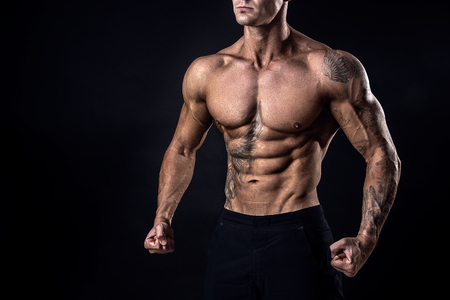 Unrecognizable Strong bodybuilder with six pack. Bodybuilder man with perfect abs, shoulders,biceps, triceps and chest, personal fitness trainer flexing his muscles ob black, dark background in studio