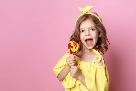 Charming girl in yellow dress with sweet lollipop on studio pink background. Stock Photo