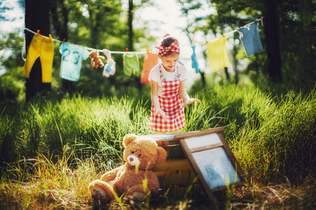 Pretty child in checkered dress headband washing toys in pelvis full of foam outdoors