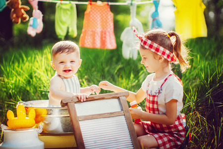 Little cute brother in apron bathing in pelvis and pretty sister in checkered dress headband laughing sitting together outdoors Standard-Bild - 103193802