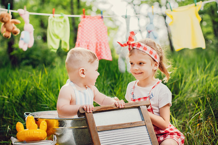Little cute brother in apron bathing in pelvis and pretty sister in checkered dress headband laughing sitting together outdoors Standard-Bild - 103193803