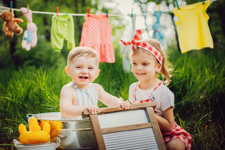 Little cute brother in apron bathing in pelvis and pretty sister in checkered dress headband laughing sitting together outdoors Standard-Bild - 103193805