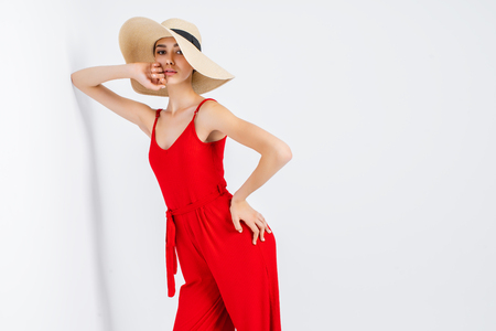 Beautiful girl in sun hat and red dress standing in studio on white background and looking at camera Stock Photo - 103193810