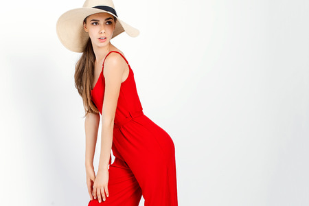 Beautiful girl in sun hat and red dress standing in studio on white background and looking away from camera