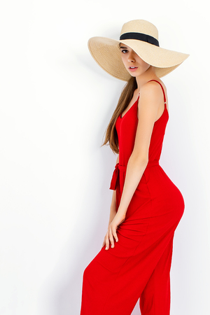 Beautiful girl in sun hat and red dress standing in studio on white background and looking at camera Stock Photo