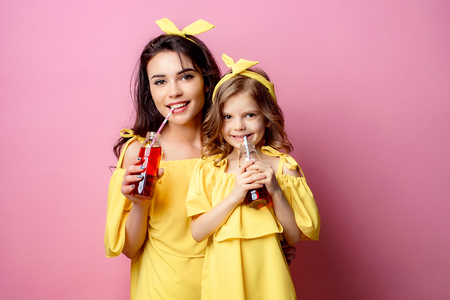 Crop view of attractive young woman with charming little girl in same yellow dresses holding red beverages smiling and looking at camera in studio on pink background. Stock Photo