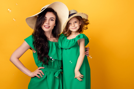 Beautiful mother standing with little girl in same green dresses and straw hats in studio with bubble looking at camera on yellow background