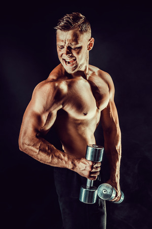 Handsome bodybuilder doing exercise with dumbbell. Studio shot.
