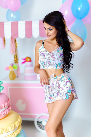 Beautiful brunette in cute short pink pajamas posing in pastel coloured studio