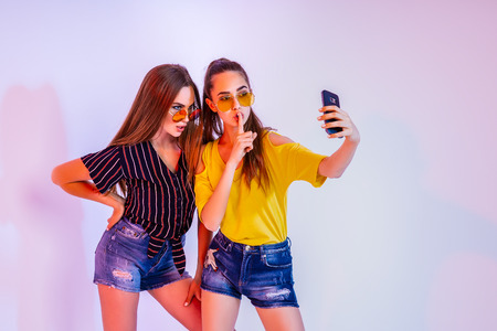 Two teenage females is sunglasses standing in studio and making selfie with smartphone on white background