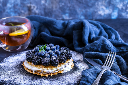 homemade waffles with blueberries and blackberries, powdered sugar on a stone plate with fruit. Shallow depth of field.