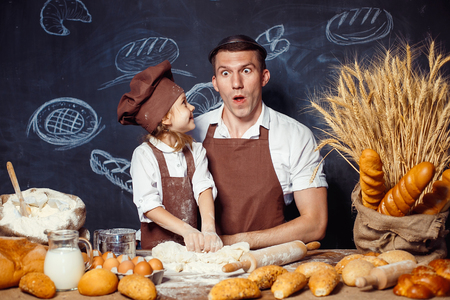 Funny pretending man with little adorable girl having fun while kneading dough and making bread