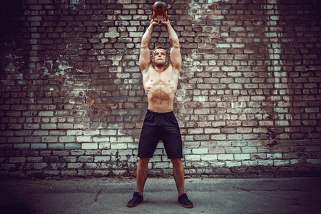 Athletic man working out with a kettlebell in front of brick wall. Strength and motivation. Outdoor workout. 写真素材