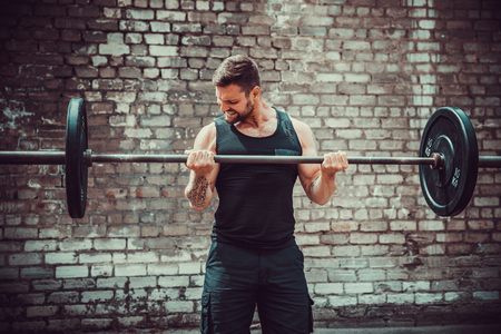 Athletic man working out with a barbell in front of brick wall. Strength and motivation. Outdoor workout. Biceps exercise. Фото со стока