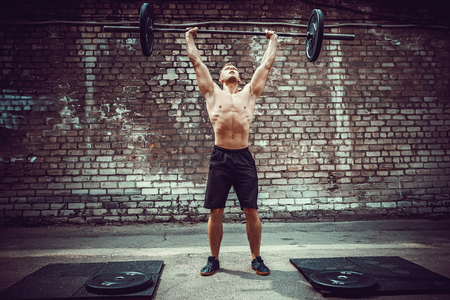Muscular fitness man doing deadlift a barbell over his head in outdoor, street gym.. Functional training. Snatch exercise 스톡 콘텐츠