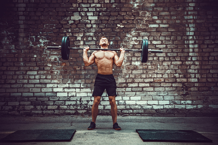 Muscular fitness man doing deadlift a barbell over his head in outdoor, street gym. Functional training. Snatch exercise. Stock Photo