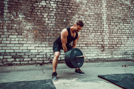 Athletic man working out with a barbell in front of brick wall. Strength and motivation. Outdoor workout. Exercise for the muscles of the back