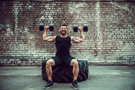 Athletic man working out with a dumbbell in front of brick wall. Strength and motivation. Outdoor workout. Exercise for the shoulder muscles, deltoid.