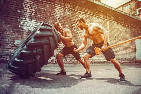 Entrenamiento de dos atletas musculosos. Hombre sin camisa de fitness muscular moviendo un neumático grande otro lo motiva y sostiene un gran hummer en el gimnasio de la calle. Levantamiento de concepto, entrenamiento de entrenamiento.