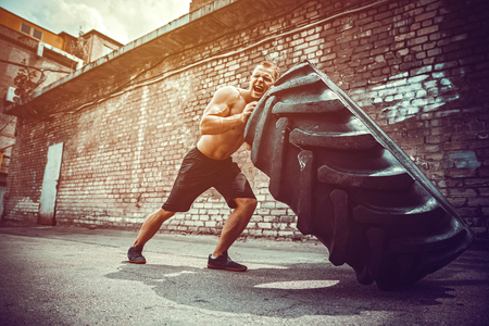 Muscular fitness shirtless man moving large heavy tire in street gym. Concept lifting, workout training. Stock Photo