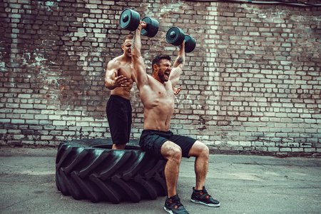 Two muscular athletes training, one raise, push the barbbell when other is motivating. Scream. Working hard. Street gym. Exercise for the shoulder muscles, deltoid. Stock Photo