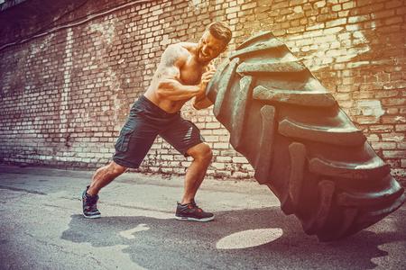 Hombre sin camisa de fitness tatuado barbudo musculoso moviendo neumático grande en el gimnasio de la calle. Levantamiento de conceptos, entrenamiento de entrenamiento. Foto de archivo