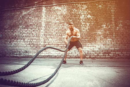 Athletic man working out with rope in front of brick wall. Strength and motivation. Outdoor workout. Imagens