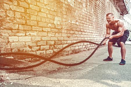 Athletischer Mann, der mit Seil vor Ziegelmauer ausarbeitet. Kraft und Motivation. Training im Freien.