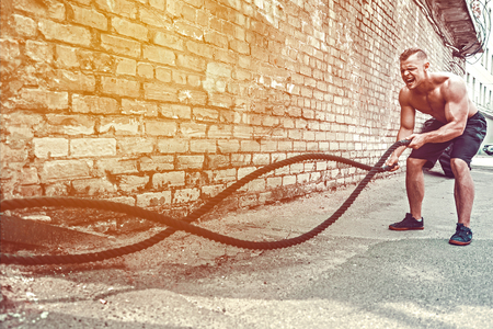Uomo atletico che risolve con la corda davanti al muro di mattoni. Forza e motivazione. Allenamento all'aperto.