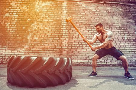 Sport Fitness Man raakt wielband met Hammer Sledge Crossfit Training, jonge gezonde kerel sportschool interieur BUITEN
