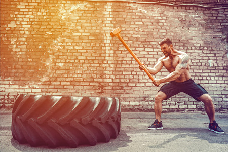Uomo di forma fisica di sport che colpisce la gomma della ruota con l'allenamento di Crossfit della slitta del martello, interno della palestra del giovane ragazzo sano FUORI
