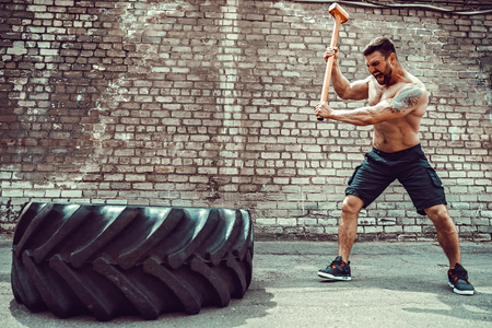 Sport Fitness Man Hitting Wheel Tire With Hammer. Sledgehammer Training. Young Healthy Guy. Outdoor Gym