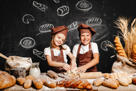 Adorable girl with brother in aprons on table with bread loaves making fresh dough and having fun