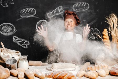 cute boy in apron and hat throwing flour powder in air having fun while making dough.