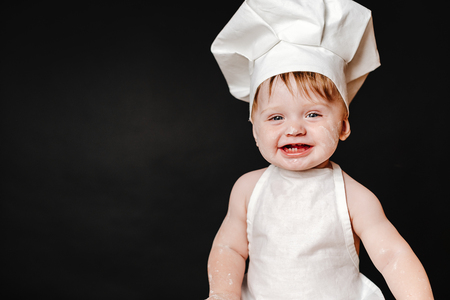 Charming toddler baby in hat of cook and apron laughing happily 版權商用圖片