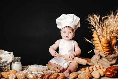 Charming toddler baby in hat of cook and apron sitting on table with bread loaves and cooking ingredients laughing happily