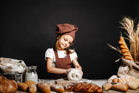 Charming little girl in apron and hat standing at table kneading bread dough and having fun spending time cooking