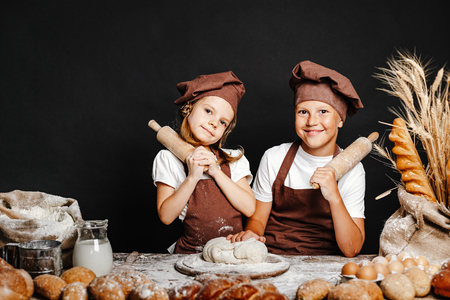Adorable girl with brother in chief hats and aprons cooking at table with bread loaves making fresh dough and having fun 版權商用圖片