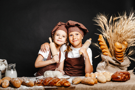 Adorable girl with brother in chief hats and aprons cooking at table with bread loaves making fresh dough and having fun 写真素材