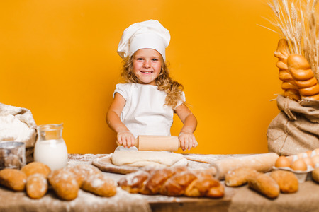 Charming little girl with curly hair in white apron and hat standing at table kneading bread dough and looking at camera. KId in good mood, having fun.