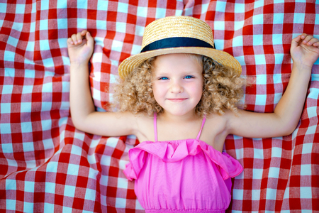 Small curly-haired girl in a straw hat lies on a checkered carpet on the street, a sluggish smile. concept of summer recreation, joy, happiness