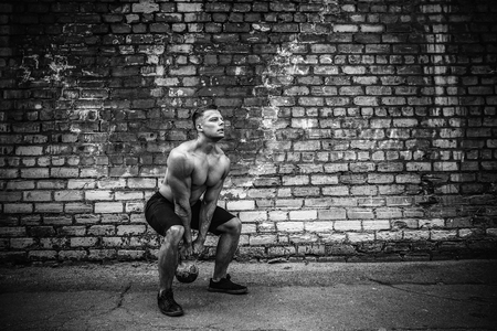 Athletic man working out with a kettlebell in front of brick wall. Strength and motivation. Outdoor workout. Stock Photo