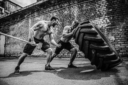 Training für zwei muskulöse Athleten. Muscle Fitness hemdloser Mann, der großen Reifen bewegt, andere motivieren ihn und halten großen Hummer im Straßengymnastikraum. Konzept heben, Training trainieren. Standard-Bild